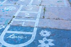 Hinkelspels op een asfaltvloer met krijttekeningen van aantallen en Stock Fotografie