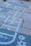 Hinkelspels op een asfaltvloer met krijttekeningen van aantallen en Royalty-vrije Stock Afbeeldingen