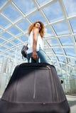 Hinten von der jungen Frau der glücklichen Reise, die mit Koffer in der Station geht lizenzfreie stockfotografie