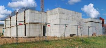 Hinter Eisenmasche ist der Zaun ein konkreter Kasten eines eben construc Stockfotos