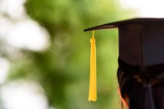 Hinter Foto der Universität trägt Absolvent Kleid und schwarze Kappe, YE lizenzfreies stockfoto