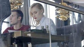 Hinter Glas im Café ist Paarsitzen und engagiert in jeder von Besetzungen stock video footage