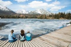 Hintere Ansicht ?ber drei weibliche Touristen, die durch gefrorenes Gebirgsla sitzen stockfotos