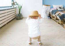 Hintere Ansicht über ein kleines Mädchen in einem Strohhut Das Baby spielt im hellen Raum, zuhause Lizenzfreies Stockbild