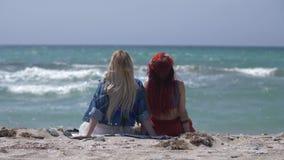 Hintere Ansicht über zwei junge Frauen gekleidet in boho Art und im Haben eines Restes auf dem Strand stock video footage