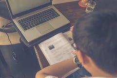 Hintere Ansicht asiatischen studierenden Englisch mit Laptop und Arbeitsbuch stockbilder