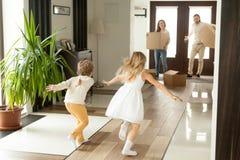 Hintere Ansicht an den Kindern, die zu den Eltern an beweglichem Tag laufen stockbilder