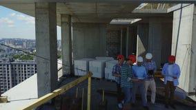 Hintere hintere Ansicht der Antenne der Gruppe Erbauer auf Baustelle, Ingenieure am Bauobjekt Plan des Projektes besprechend stock video