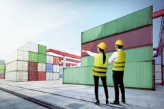Hintere Ansicht der asiatischen Arbeitskraft zwei mit Sicherheitsweste, -Schutzhelm und -Schutzmaske das Dock zeigend und betrach stockbild
