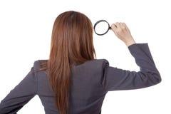 Hintere Ansicht der asiatischen Geschäftsfraugebrauchslupe Lizenzfreies Stockbild