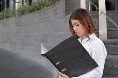 Hintere Ansicht der attraktiven jungen asiatischen Geschäftsfrau, die Dokumentenpapier auf Ringmappe bevor dem Treffen Gehweg des lizenzfreies stockfoto