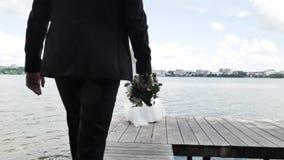 Hintere Ansicht: Der Bräutigam geht zur Braut mit einem Blumenstrauß von Blumen am Pier stock footage
