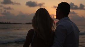 Hintere Ansicht der Braut und des Bräutigams, die im Urlaub Sonnenuntergang auf tropischem Strand nahe Balustrade genießen Umarme stock video footage