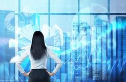 Hintere Ansicht der Brunettefrau, die heraus das Fenster im panoramischen Büro in New York schaut Finanzdiagramme sind über dem w Stockbilder
