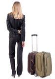 Hintere Ansicht der durchdachten Geschäftsfrau, die mit suitcas reist. Stockbild