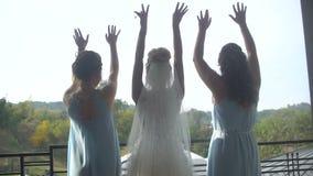 Hintere Ansicht der eleganten Braut im langen Luxuskleid und ihre zwei Brautjungfern in den blauen Kleidern tanzen glücklich an stock footage