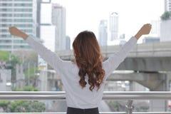 Hintere Ansicht der erfolgreichen jungen Aian-Geschäftsfrau, die ihre Hände am städtischen Gebäudestadthintergrund anhebt Stockfotografie
