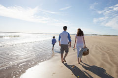 Hintere Ansicht der Familie gehend entlang Strand mit Picknick-Korb Lizenzfreies Stockfoto