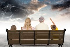 Hintere Ansicht der Familie sitzend auf Bank gegen Sternkonstellationen Lizenzfreie Stockfotografie