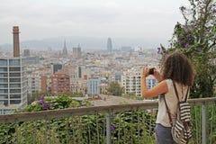 Hintere Ansicht der fotografierenden Ansicht der Frau von Barcelona auf der Kamera Lizenzfreie Stockfotografie