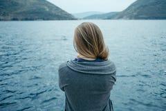 Hintere Ansicht der Frau allein denkend und das Meer mit aufpassend lizenzfreie stockfotografie