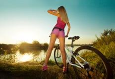 Hintere Ansicht der Frau auf dem Fahrrad, das bei Sonnenuntergang sich entspannt Stockbild