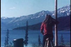 Hintere Ansicht der Frau ihr Haar durch See in Alaska bürstend stock footage