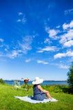 Hintere Ansicht der Frau im Hut, der auf der Seeküste mit Weinlese sitzt Lizenzfreies Stockfoto