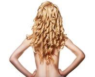 Hintere Ansicht der Frau mit dem gelockten langen blonden Haar Stockfotos