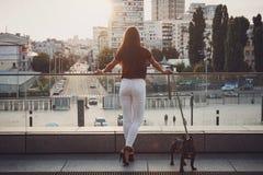 Hintere Ansicht der Frau mit französischer Bulldogge in der Stadt lizenzfreie stockfotografie