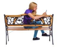 Hintere Ansicht der Frau sitzend auf Bank und Blicken am Schirm die Tablette Lizenzfreie Stockfotos
