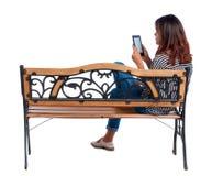 Hintere Ansicht der Frau sitzend auf Bank und Blicken am Schirm die Tablette Lizenzfreie Stockfotografie