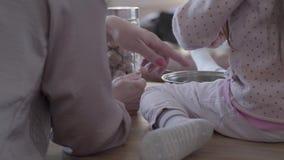 Hintere Ansicht der Frau und des kleinen Kindes, die in der Küchentisch- und Mutterunterrichtstochter sitzen, wie man kocht stock video