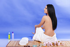 Hintere Ansicht der Frau und tragendes Tuch, die auf dem Boden, lokalisiert sitzt Lizenzfreies Stockfoto