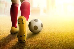 Hintere Ansicht der Fußballspielerfrau im orange Trikot, das den Ball tritt stockbild