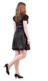 Hintere Ansicht der gehenden Brunettefrau im schwarzen Kleid. Lizenzfreie Stockfotografie