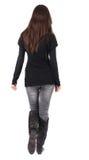 Hintere Ansicht der gehenden Frau in den Jeans und in der Strickjacke Stockfotografie