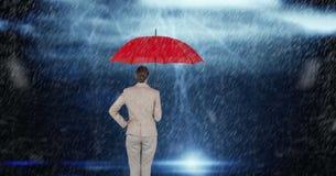 Hintere Ansicht der Geschäftsfrau den roten Regenschirm halten, der im Regen steht Stockfotos