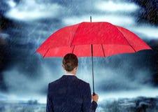 Hintere Ansicht der Geschäftsfrau roten Regenschirm im regnerischen sesaon tragend Stockfotografie