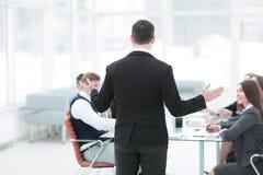 Hintere Ansicht der Geschäftsmann hält eine Anweisung mit dem Geschäftsteam stockfoto