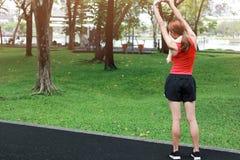 Hintere Ansicht der gesunden jungen Asiatin, die ihre Hände vor Lauf im Park am Morgen ausdehnt Training und Übungskonzept stockbild