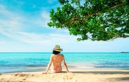 Hintere Ansicht der glücklichen jungen Asiatin im rosa im entspannenden Badeanzug und Strohhut und Feiertag am tropischen Paradie lizenzfreie stockfotografie