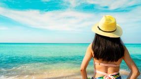 Hintere Ansicht der glücklichen jungen Asiatin mit Strohhut Feiertag am tropischen Paradiesstrand sich entspannen und genießen Mä lizenzfreies stockbild