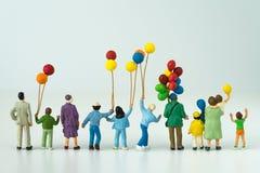 Hintere Ansicht der glücklichen Miniaturfamilie, die Ballone mit Weiß hält Lizenzfreies Stockbild