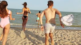 Hintere Ansicht der Gruppe Freunde ziehen Betrieb in das Meerwasser auf Sonnenuntergang aus und werfen Hemden auf dem Strand Nett stock footage