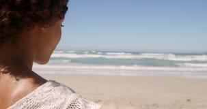 Hintere Ansicht der jungen Afroamerikanerfrau, die auf Strand im Sonnenschein 4k sich entspannt stock video footage