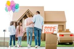 hintere Ansicht der jungen Familie bewegend in neues cardbord Haus lizenzfreie stockfotografie