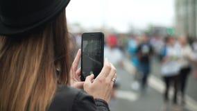Hintere Ansicht der jungen Frau, die den Smartphone zum Machen von den Fotos der großen Gruppe von Personen den Marathon laufen l stock video