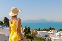 Hintere Ansicht der jungen Frau im gelben Kleid in Sidi Bou Said, Tunis, Tunesien lizenzfreies stockfoto