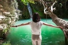 Hintere Ansicht der jungen Frau mit den Händen genießen oben Wasserfall auf beauti Lizenzfreies Stockfoto